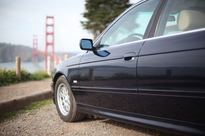 BMW 525i close-up with Golden Gate Bridge in the distance