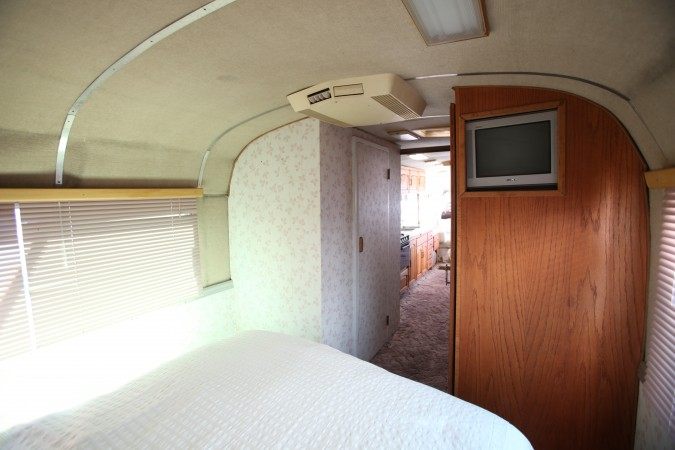 1967 MCI 5A Challenger Bus Conversion, bedroom looking toward bathroom and TV