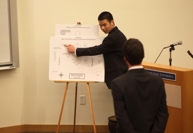 Marcus Wong, playing a police officer, explains exhibit to Havel Weidner, playing attorney for the prosecution, at San Francisco Mock Trial 2012 finals, February 23, 2012.