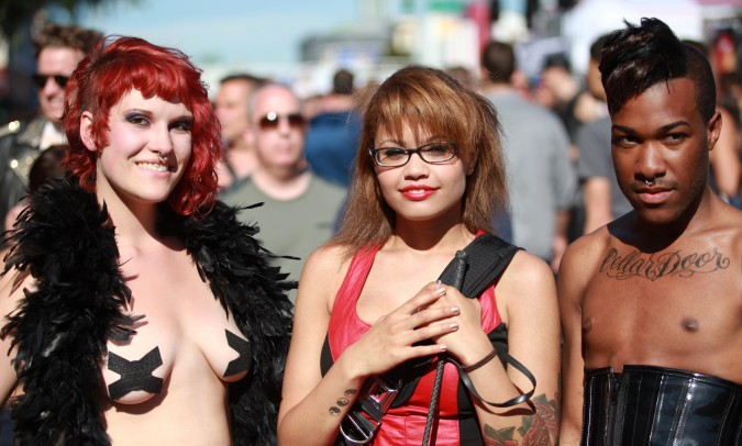 Two women and a man pose for the camera at the San Francisco Folsom Street Fair, September 23, 2012.