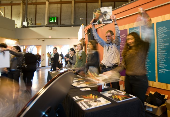 Staff members handing out free promotional posters for the new Exploratorium that will open later this year near the Ferry Building in downtown San Francisco. Picture taken January 2, 2013.