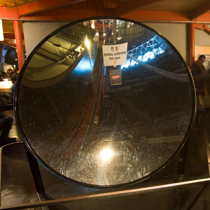 Large parabolic shaped mirror demonstrates that light and heat can be focussed to a point. Note electric space heater pictured in the center of the mirror.