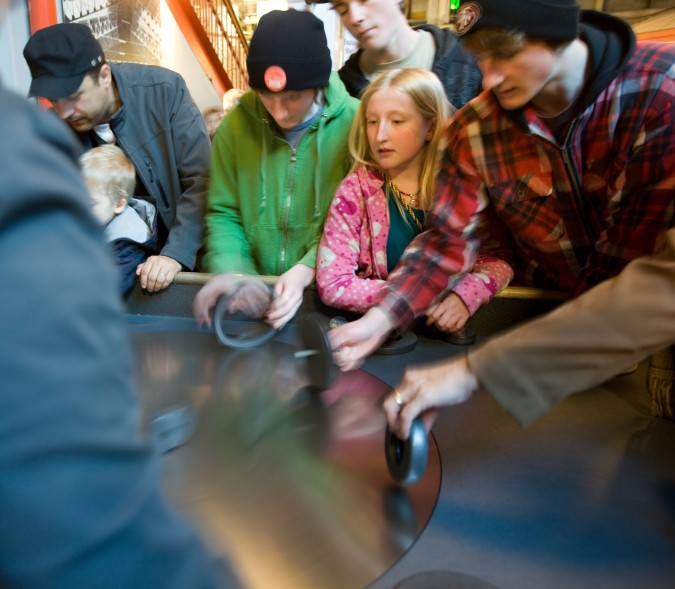 The round disk in the table surface is rotating. Visitors try to place metal wheels onto the surface of the quickly rotating disk. If successful, the wheels roll mostly in place relative to the visitor. I remember this exhibit from my childhood.