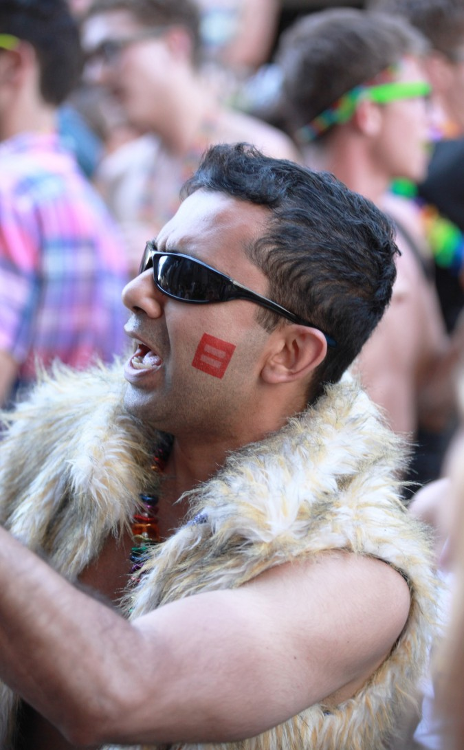 San Francisco Pride Parade and Celebration 2013 - picture 71, June 30, 2013, man with red equality stamp on his face. This year numerous people temporarily replaced their Facebook Profile picture with an image of this equality stamp.
